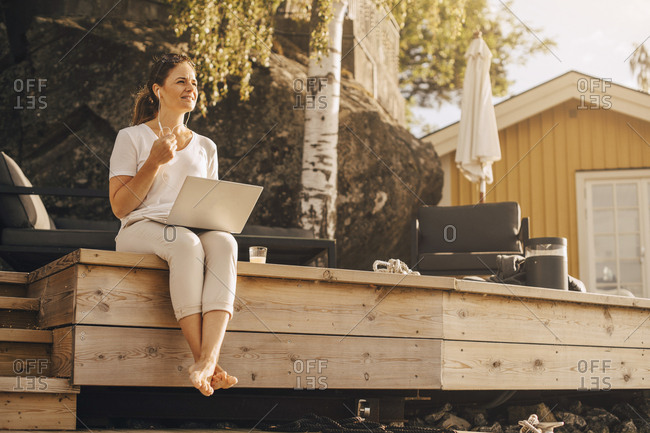Full length of woman talking on headphones while using laptop at holiday villa