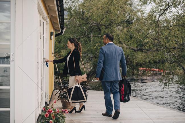 Full length of mature couple unlocking door at holiday villa by lake