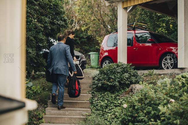 Rear view of business couple walking towards cars at holiday villa