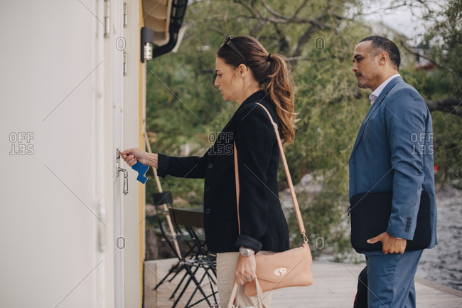 Mature business couple unlocking door at holiday villa