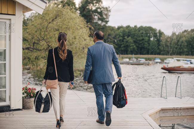 Rear view of mature couple walking at holiday villa by lake