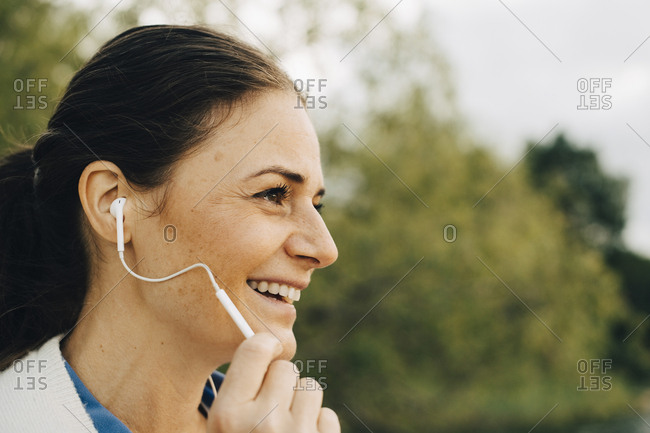 Close-up of smiling woman talking through headphones while looking away