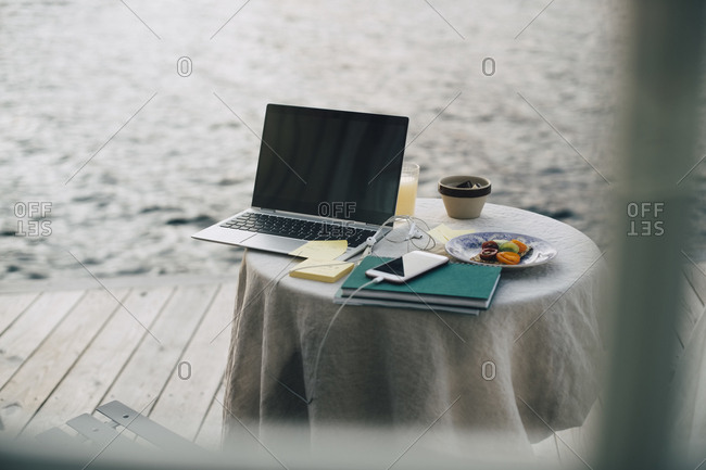 Laptop and smart phone with books by breakfast on table seen through window at holiday villa