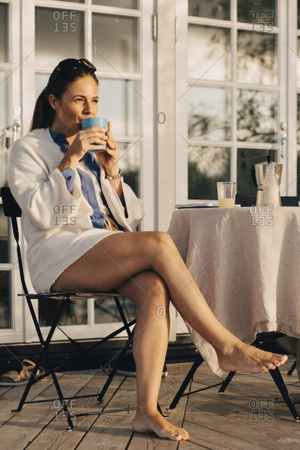 Low angle view of mature woman drinking coffee while sitting at patio in holiday villa