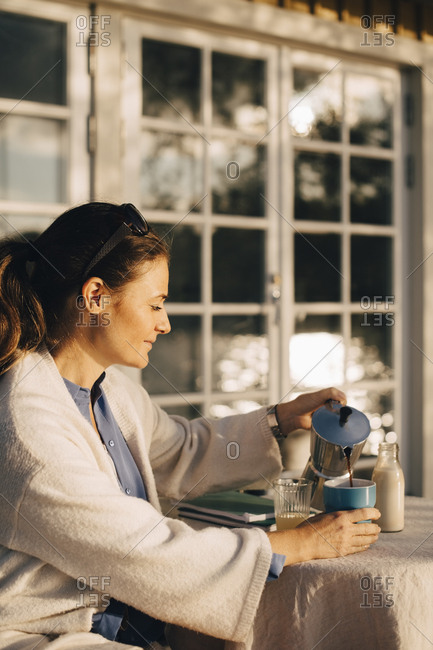 Mature woman pouring coffee at table in holiday villa