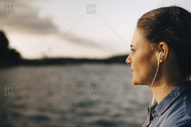 Close-up of thoughtful woman listening music through headphones by lake in summer vacation