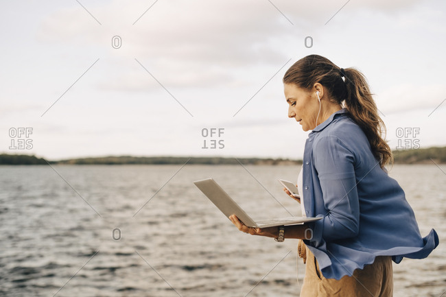 Confident mature woman using laptop while talking on mobile phone by lake
