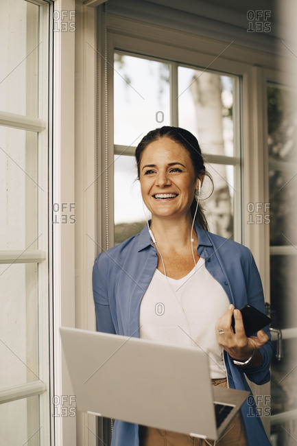 Portrait of smiling woman talking through headphones while using laptop at holiday villa