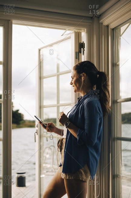 Thoughtful smiling woman talking through headphones on smart phone while standing at holiday villa