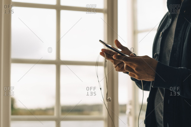 Midsection of mature man using mobile phone while standing in holiday villa