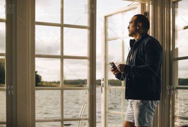 Thoughtful mature man using mobile phone while standing at doorway in holiday villa