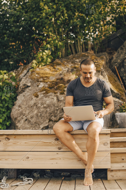 Full length of mature man using laptop while sitting on patio against trees