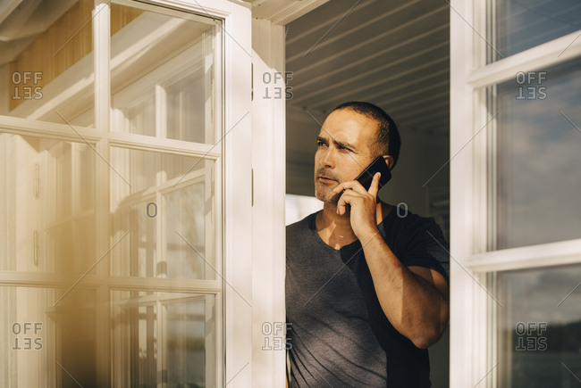 Thoughtful man talking on smart phone while standing at window