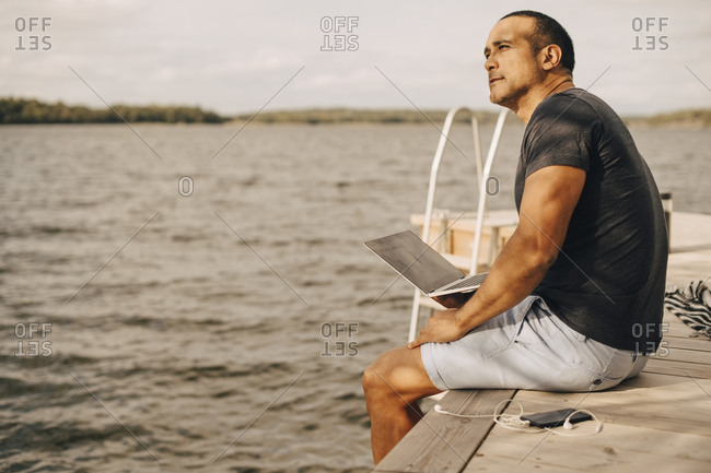 Thoughtful mature man sitting with laptop on jetty over lake