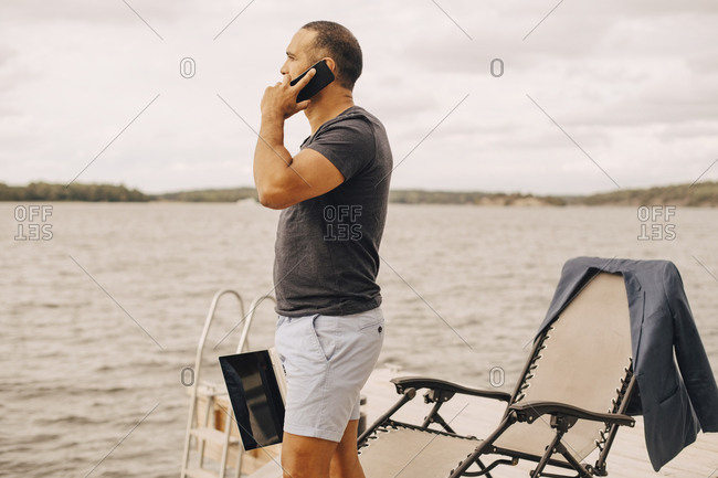 Man with laptop talking on smart phone while standing on jetty by lake against sky