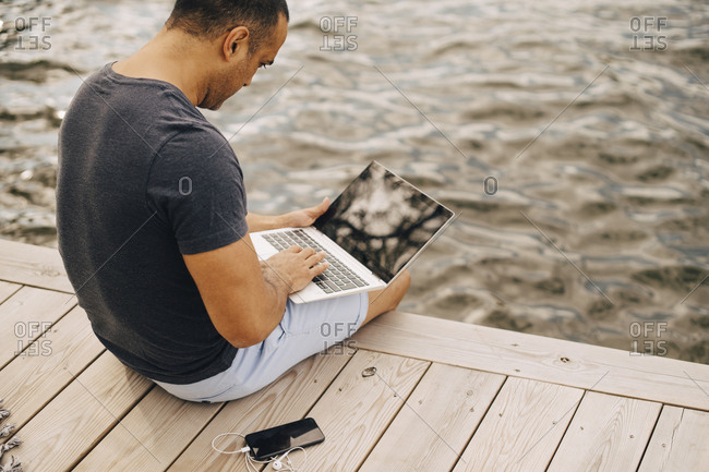 Mature man using laptop while sitting on jetty over lake