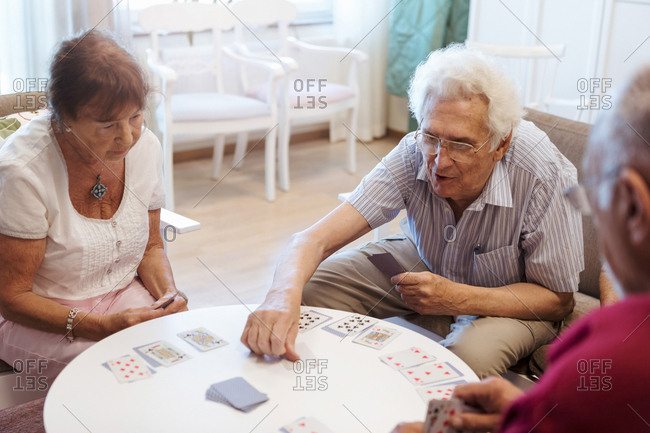 Senior people playing cards at table in retirement home
