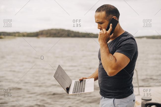 Mature man talking on mobile phone while using laptop by lake