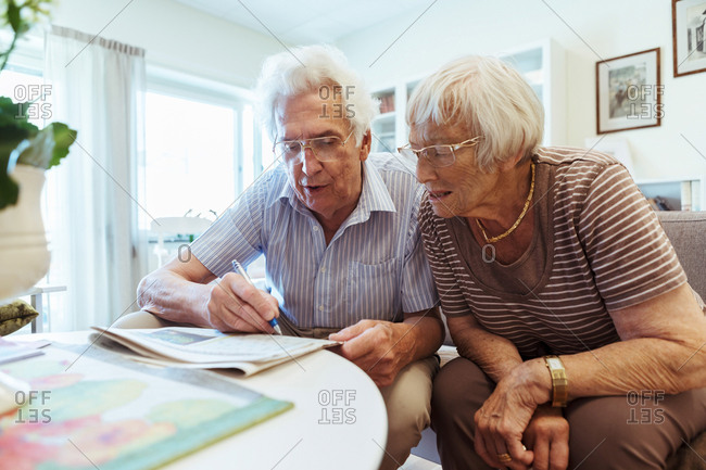 Senior couple doing crossword puzzle in newspaper at nursing home