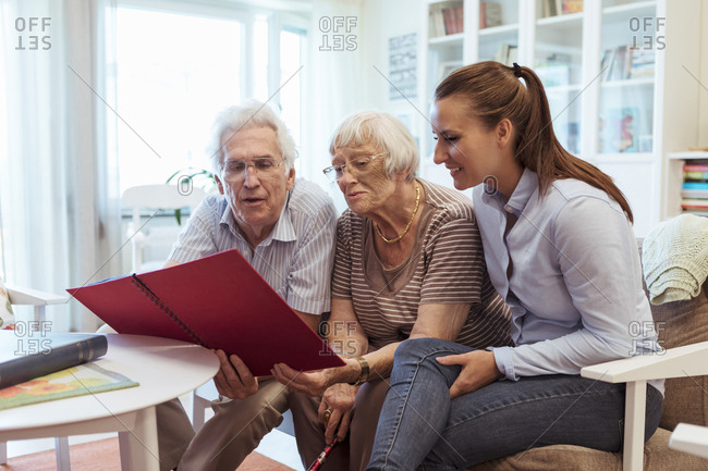 Young woman with grandparents looking at photo album in nursing home