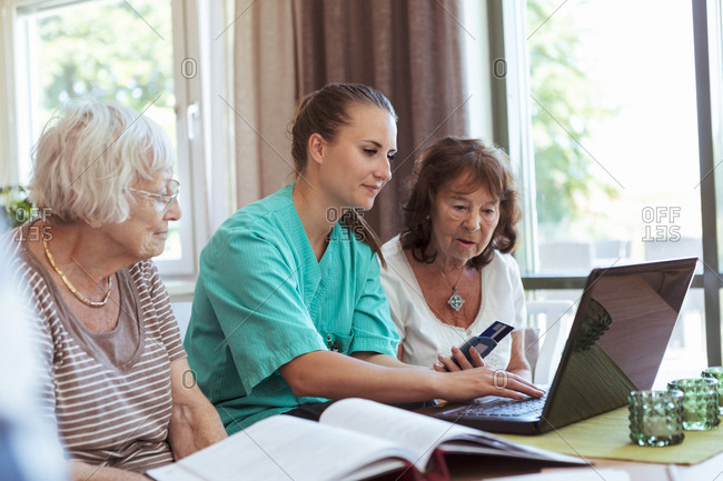 Nurse with senior women buying medicine online using laptop and credit card at nursing home