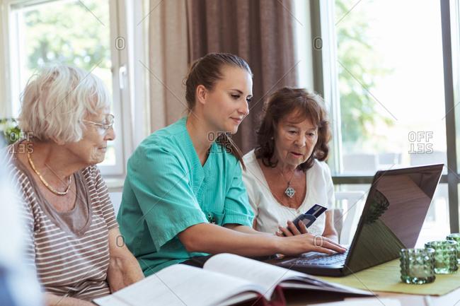 Nurse with senior women buying medicine online using laptop and credit card at nursing home