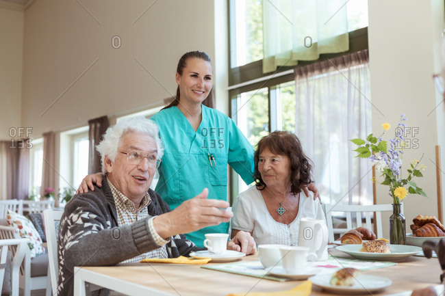 Smiling healthcare worker and senior woman listening to man during breakfast at home