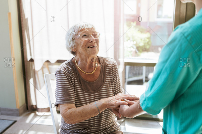 Smiling senior woman holding hands of healthcare worker at nursing home