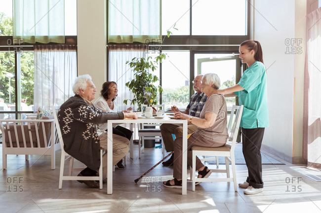 Nurse massaging shoulders of senior woman having breakfast with friends at nursing home