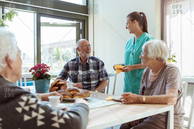 Smiling senior man and nurse talking while having breakfast at nursing home