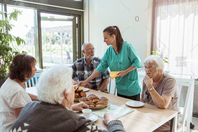 Elderly care nurse serving meal to people at table in nursing home