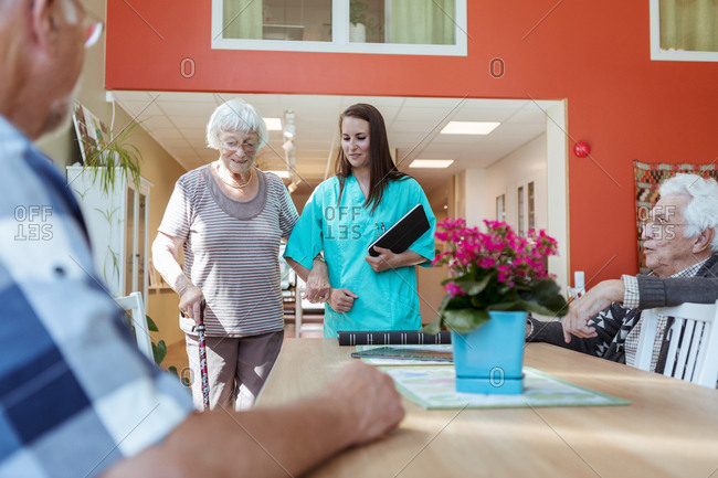 Senior woman and nurse walking arm in arm towards friends at nursing home