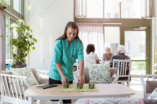 Female caretaker arranging table with senior people in background at nursing home