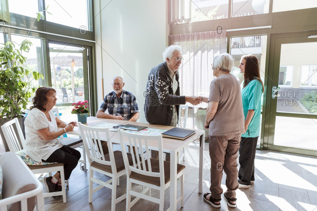 Senior man and woman shaking hands near friends and nurse at nursing home