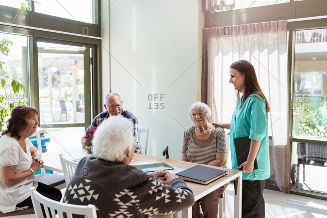 Female healthcare worker talking with elderly people at nursing home
