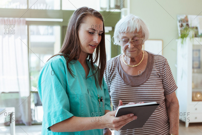 Female healthcare worker showing digital table to senior woman in nursing home