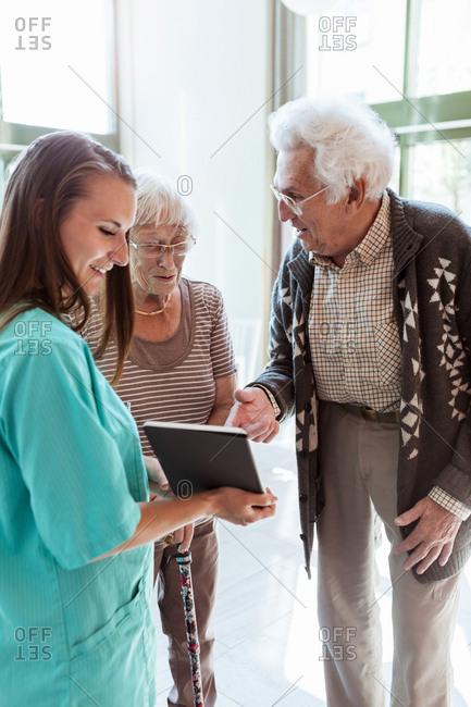 Young female nurse showing digital tablet to senior couple at nursing home