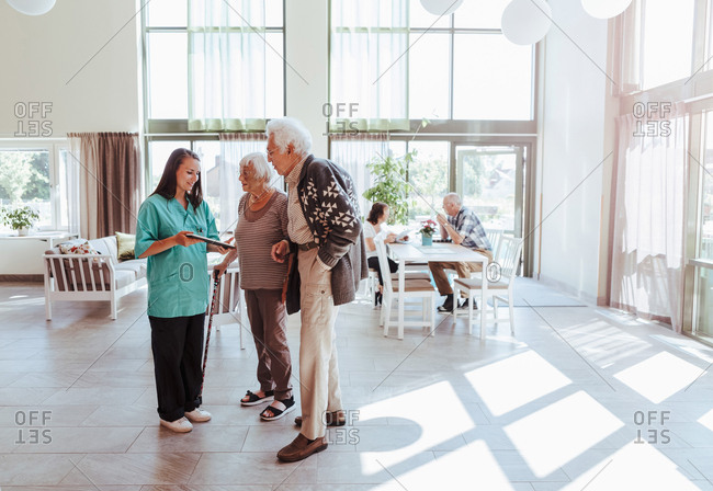 Full length of nurse showing digital tablet to senior couple at nursing home
