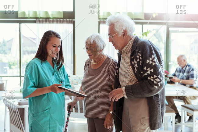 Young caretaker showing digital tablet to senior couple at nursing home