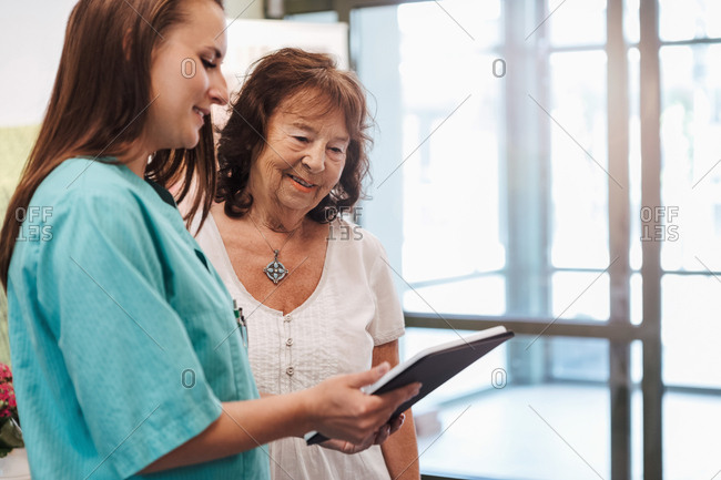 Young nurse and senior woman using digital tablet in nursing home