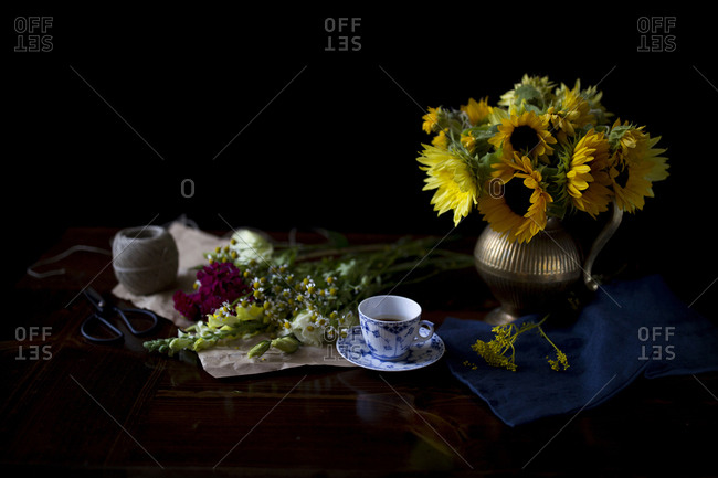 Sunflowers in a brass vase with a blue coffee mug on a table