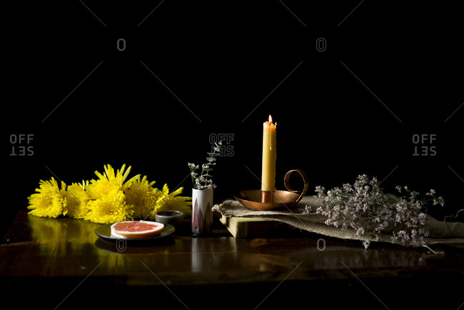 Beeswax candle with yellow flowers on a wooden table