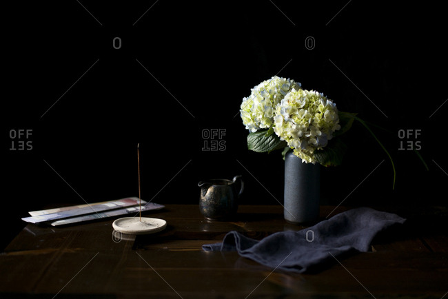 Hydrangea bouquet in a blue dutch vase with campfire incense on a table