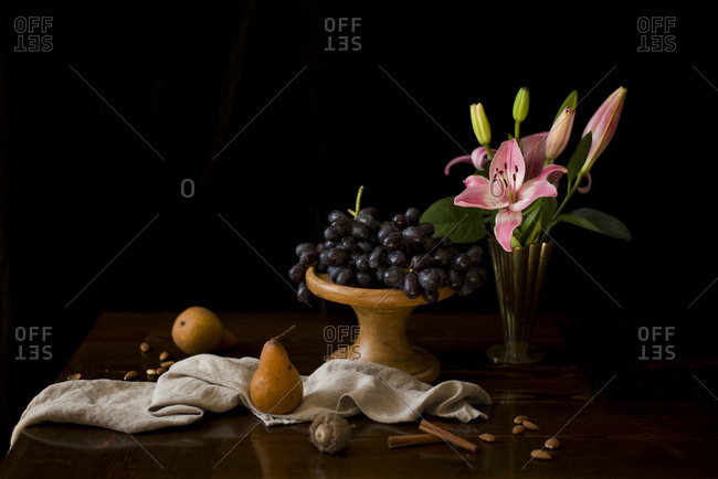 A bunch grapes on a wooden cake stand with lilies and bosc pears on a table