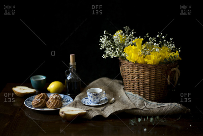 Yellow daffodils in a woven basket with coffee and dessert on a table