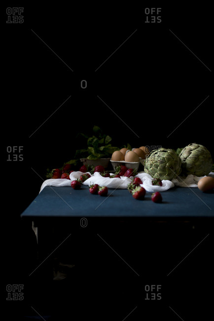 Various fresh farm vegetables and fruits on a table in a dark background