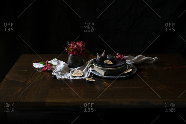 Figs on a rustic ceramic plate with a red alstroemeria bouquet on a wooden table