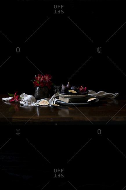 Figs on a rustic ceramic plate with a red alstroemeria bouquet in a dark background