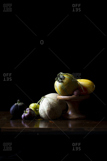Fresh various summer melon and squash on a wooden tray in a dark background