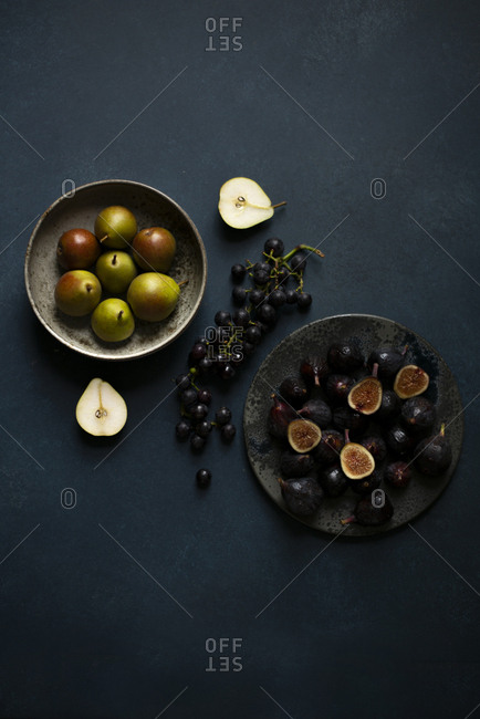 Top view of figs and pears on rustic ceramic plates on a table